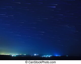 Stars leave traces above the city. Time Lapse. 4x3