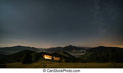 Stars moving in night sky over mountains and foggy rural landscape at moonlight. Night to day time lapse dolly shot