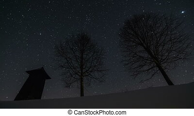 Stars moving in night sky over wooden bell-tower and trees silhouette in winter, astronomy time lapse, dolly shot