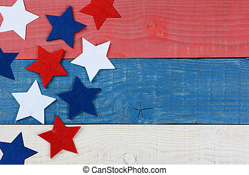 High angle shot of red white and blue stars on a patriotic picnic table. The wood table is painted red, white and blue. Perfect for Memorial Day or 4th of July themes, with copyspace.