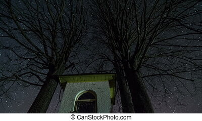 Stars rotating over chapel and lime trees silhouette in night sky, astronomy time lapse, dolly shot,