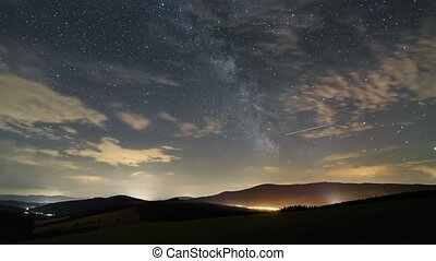 Stars sky with milky way galaxy and clouds moving over beautiful landscape time lapse