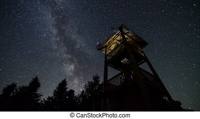 Stars sky with milky way turning over lookout tower time lapse. Astronomy starry night