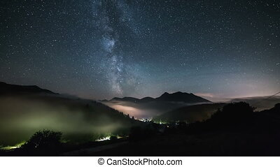 Stars with milky way galaxy moving over mountains above foggy valley in starry sky night time lapse
