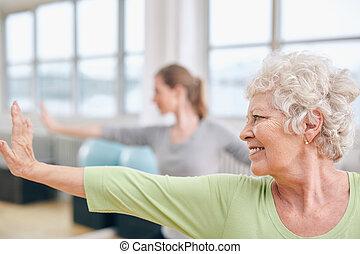 starsza kobieta, czyn, rozciąganie, trening, na, yoga klasa