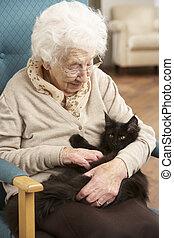 starsza kobieta, odprężając, w krześle, w kraju, z, pieszczoch, kot
