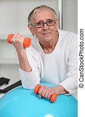 starsza kobieta, podnoszenie obciąża, w, sala gimnastyczna