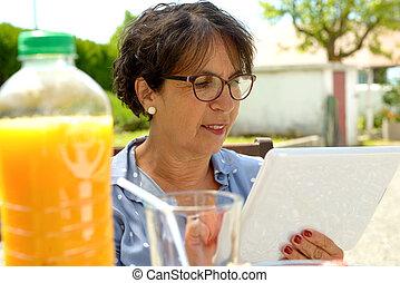 starsza kobieta, używając, tabliczka, ., posiedzenie, w ogrodzie