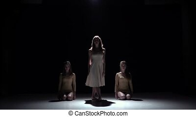 Start contemporary dance of three girls in white dresses, on black, shadow, slow motion