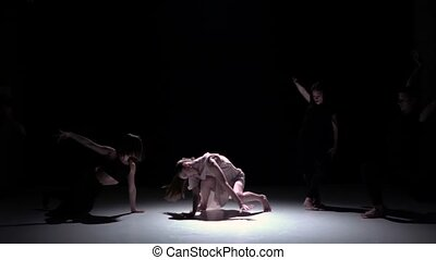 Start contemporary dance performance of five dancers on black, shadow, slow motion