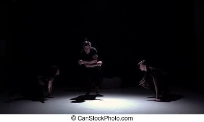 Start graceful contemporary dance of four dancers on black, shadow, slow motion