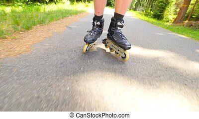 Start inline skating on smooth asphalt in the forest. Close up view to light skin man legs quick movement of inline boots.