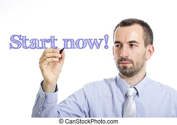 Start now! - Young businessman writing blue text on transparent surface