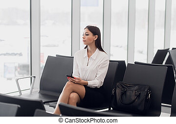 Start of her journey. Beautiful young woman looking out window at flying airplane while waiting boarding on aircraft in airport lounge.