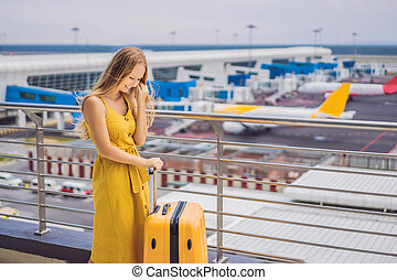 Start of her journey. Beautiful young woman ltraveler in a yellow dress and a yellow suitcase is waiting for her flight