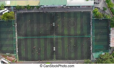 Start of training before a football match. Game process. Aerial shot of a small soccer field, many teams playing soccer ball outdoors, top view. Green field with markings, players running with ball