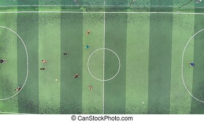 Start of training before a football match. Game process. Aerial shot of a small soccer field, two teams playing soccer ball outdoors, top view. Green field with markings, players running with ball