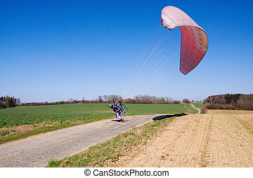 Start powered paraglider pilot in flight over the landscape