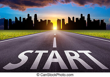 Start text on long road. A long straight road and cityscape at sunset.