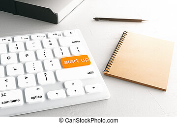 Start up button - Closeup of white keyboard with orange...