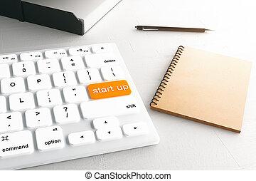 Start up button - Closeup of white keyboard with orange...