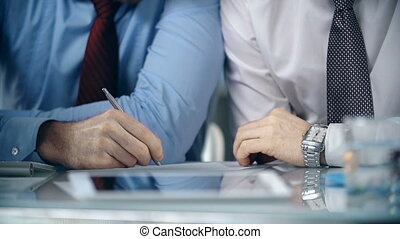 Mid-section of two businessmen writing at the desk
