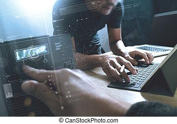Start Up Programming Team. Website designer working digital tablet dock keyboard and computer laptop with smart phone and compact server on mable desk, light effect