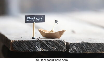 start up text and a paper boat on a wooden table