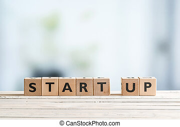 Start up sign on a desk - Start up sign on a wooden office...