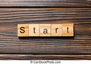 Start word written on wood block. Start text on wooden table for your desing, concept