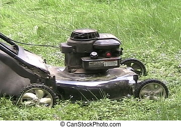 Starting a Lawn Mower - A close up on a man starting a lawn...