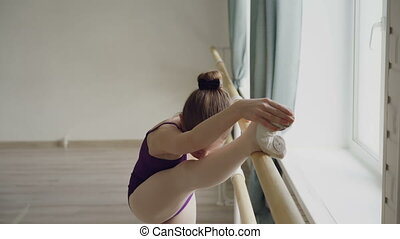 Starting ballet dancer is practising movements stretching...