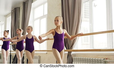 Starting ballet-dancers are doing exercises at ballet barre...