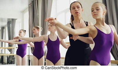 Starting ballet dancers are practising arm movements during...