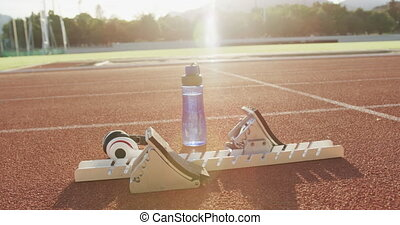 Starting blocks, a bottle of water and headphones belonging to an athlete lying in the sun on an outdoor running track at a sports stadium, with lens flare