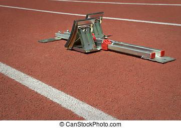 Starting blocks on red tartan running track - Starting...