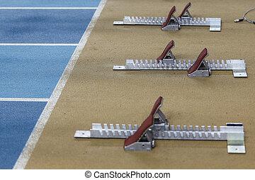 Starting blocks in tart line over running track