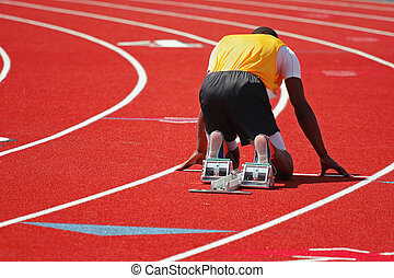Starting line - a runner on a red track in the starting...
