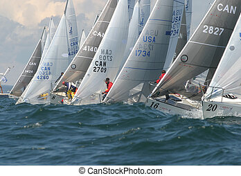 J/24 sailboats racing down the start line with only a second left. Photo taken at the 2004 J/24 Nationals.