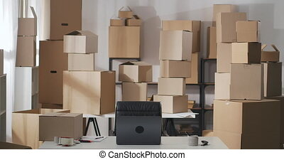 Starting small business, SME owner carries box of goods on the table to deliver to customers. Man using laptop in a warehouse.