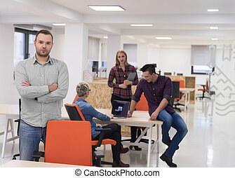 startup business, businessman portrait at modern office, team brainstorming in background