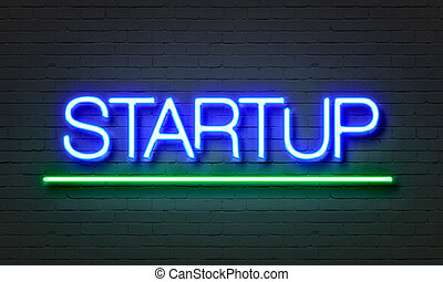 Startup neon sign on brick wall background.