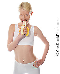Starving sexy woman eating banana, half-peeled