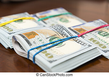 Stashes of hundred dollar bills on wooden table