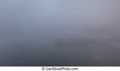 Static drone shot of fog surrounding Pismo Beach pier. Eerie hazy morning conditions.