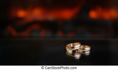 Static frame Two gold rings against the fire from the fireplace Glass table black dark background