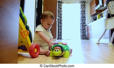 static shot, cute seven months old baby boy playing with educational toys on the floor happy childhood,early development concept