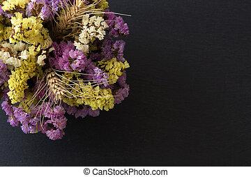Statice flowers on black stone background