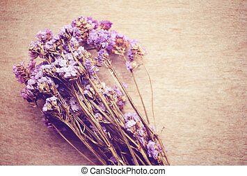 Statice flowers on wooden background with retro filter effect