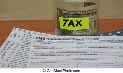 jar with tax label one dollar note and 1040 form moving on the wind